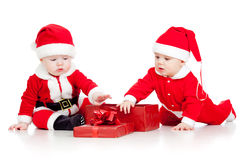 Funny kids in Santa Claus clothes with gift box Stock Image