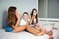Funny kids are sitting in bed and eating donuts. Horizontal Stock Photo