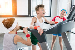 Funny kids in sportswear training on treadmill at gym together. Children sport concept royalty free stock image