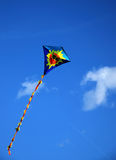 Funny Kite. A funny flying kite with a smiling sun face. Blue sky. Image with copy space stock image