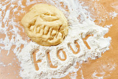 Funny knead dough and flour on wooden table with text Royalty Free Stock Photos