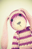 Funny knitted rabbit toy portrait, vintage toned Stock Photo