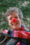 Funny Lady. A happy, smiling woman with a big red nose and colorful scarf Royalty Free Stock Images