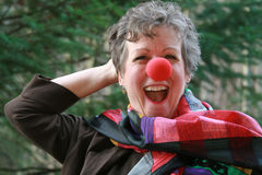 Funny Lady. Happy lady with a red clown nose and colorful scarf Stock Photo