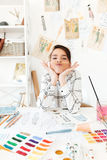 Funny lady fashion illustrator sitting at the table and joking. Image of young funny lady fashion illustrator sitting at the table and joking holding pencil with Stock Photos