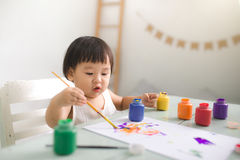 Funny laughing asian baby girl drawing with colorful pencils at. Home Royalty Free Stock Photography