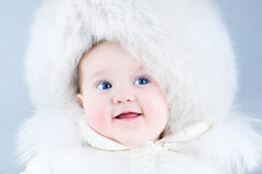 Funny laughing baby in a big white fur hat Stock Photos