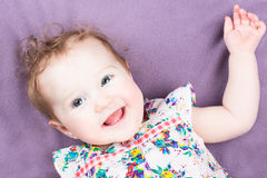 Funny laughing baby girl in a colorful dress Stock Image