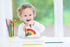 Funny laughing baby girl drawing at a white desk Royalty Free Stock Image