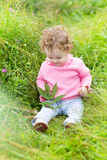Funny laughing baby girl playing in a blooming garden Stock Photography