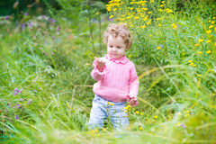 Funny laughing baby girl playing in a blooming garden Stock Images