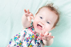 Funny laughing baby girl playing on a green blanket Stock Image