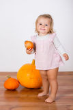 Funny laughing baby girl playing with a huge pumpkin Stock Images