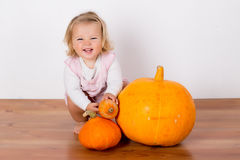 Funny laughing baby girl playing with a huge pumpkin Royalty Free Stock Photography
