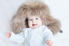 Funny laughing baby girl wearing huge winter hat Stock Photography