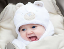 Funny laughing baby in a teddy bear hat in stroller Royalty Free Stock Image