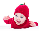 Funny laughing baby wearing knitted red apple hat Stock Photos