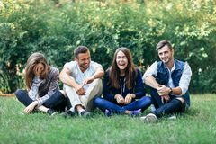 Funny laughing friends sitting on grass with crossed legs. Caucasian young women and men having fun on lawn on warm summer day. Happy beautiful healthy people Royalty Free Stock Image