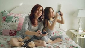 Funny laughing girl with happy young mother have fun while playing computer console games on TV sitting on bed at home stock footage