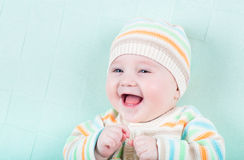 Funny laughing girl in a knitted sweater and hat o Royalty Free Stock Images