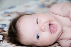 Funny laughing infant portrait, happy smiling baby winking Stock Images