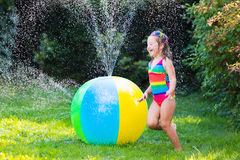 Funny laughing little girl playing with toy ball garden sprinkler Royalty Free Stock Photography