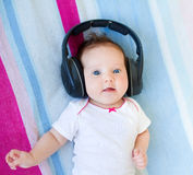 Funny laughing newborn baby listening ear phones Stock Photo