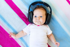 Funny laughing newborn baby listening ear phones stock images