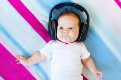 Funny laughing newborn baby listening ear phones. Funny laughing newborn baby relaxing on a colorful blanket listening ear phones Stock Images