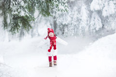 Funny laughing toddler girl running in snowy park Royalty Free Stock Photos