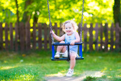 Funny laughing toddler girl swinging ride on playground Royalty Free Stock Image