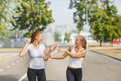 Happy friends jogging on a blurred background. Happy girl runners. Activity concept. Copy space. Royalty Free Stock Image