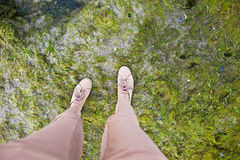 Funny legs. Boots standing on shore stone covered by green water plant Royalty Free Stock Photo