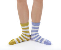 Funny legs in socks of different colors. On white background Stock Photos