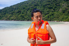 Funny Lifeguard. A male model wearing light orange life jacket with a whistle standing on the beach acting funny by the sea stock images