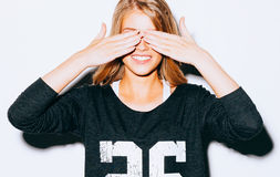 Funny lifestyle portrait beautiful blond crazy girl closes eyes with her hands , in Sweatshirt and white shorts, having fun, emoti Royalty Free Stock Image