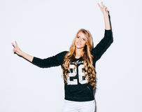 Funny lifestyle portrait of crazy girl, emotional and happy mood, having fun, chic clothes. Shows sign Victory. Spread her arms . Stock Photography