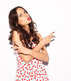 Funny lifestyle portrait of crazy girl, emotional and happy mood, having fun, chic clothes and summer dress. Shows red lips kiss. Royalty Free Stock Image
