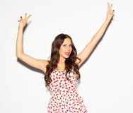 Funny lifestyle portrait of crazy girl, emotional and happy mood, having fun, chic clothes and summer dress. Shows sign Victory. S Royalty Free Stock Image