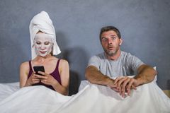 Eccentric and weird housewife with makeup facial mask and towel using mobile phone in bed and husband in desperate face expression stock photography