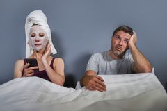 Eccentric and weird housewife with makeup facial mask and towel using mobile phone in bed and husband in desperate face expression royalty free stock photography