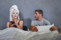 Eccentric and weird housewife with makeup facial mask and towel using mobile phone in bed and husband in desperate face expression. Funny lifestyle portrait of stock photo