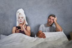 Eccentric and weird housewife with makeup facial mask and towel using mobile phone in bed and husband in desperate face expression stock images
