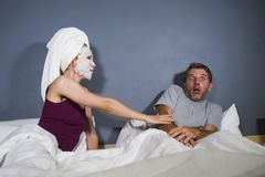 Funny lifestyle portrait of man and woman featuring weird married couple with wife in head towel and makeup face mask demanding se. Funny lifestyle portrait of royalty free stock images