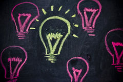 Funny lightbulb on blackboard, concept of uniqueness Stock Images