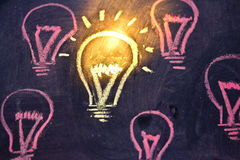 Funny lightbulb on blackboard, concept of uniqueness Stock Photos