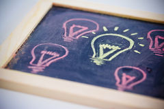 Funny lightbulb on blackboard, concept of uniqueness Royalty Free Stock Photo