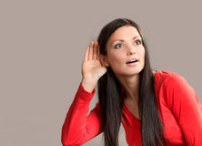 Funny listening woman. Funny portrait of a listening young woman on gray background royalty free stock image