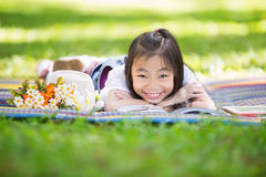 Funny little Asian girl reading and learning with tablet pc Royalty Free Stock Photo