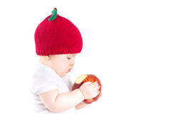 Funny little baby in an apple hat holding a big red apple Royalty Free Stock Photography